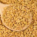 Fenugreek seeds in wooden spoon as food background